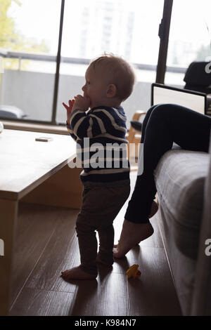 Side view of boy standing by mother sitting on sofa in livings room  at home - Stock Photo
