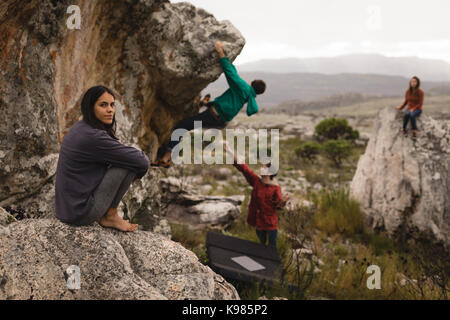 Portrait of woman sitting on rock with friends in background - Stock Photo