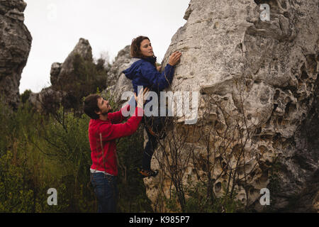 Man assisting woman in rock climbing on a sunny day - Stock Photo