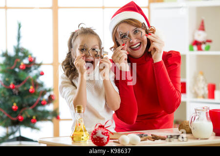 happy family mother and child have a fun preparing the dough. Woman and daughter bake christmas cookies in festival - Stock Photo