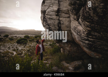 Man standing under cliff on a sunny day - Stock Photo