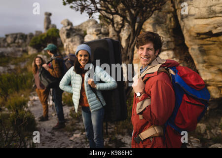 Portrait of happy friend standing with rucksack during mountaineering - Stock Photo