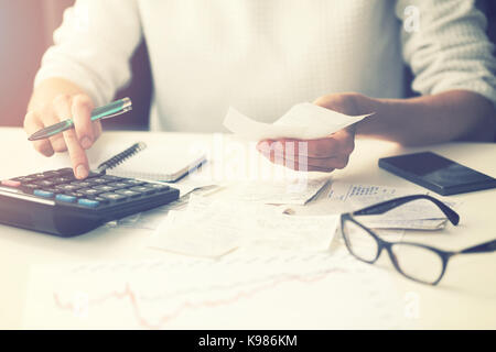 household expenses - woman calculating bills at home - Stock Photo