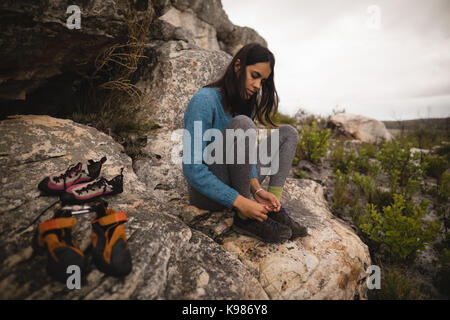 Woman wearing sports shoes on rock - Stock Photo
