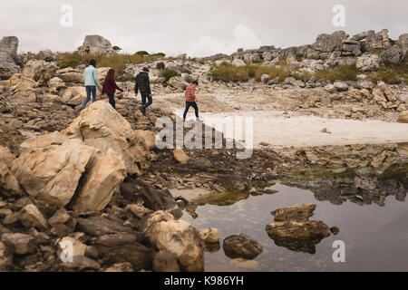 Group of friends walking near lakeside on a sunny day - Stock Photo