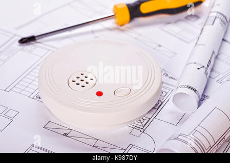 Smoke detector lying on blueprints with screwdriver in the background - Stock Photo