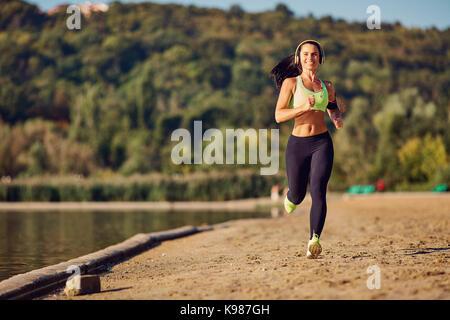 A sports girl runs through the park. - Stock Photo