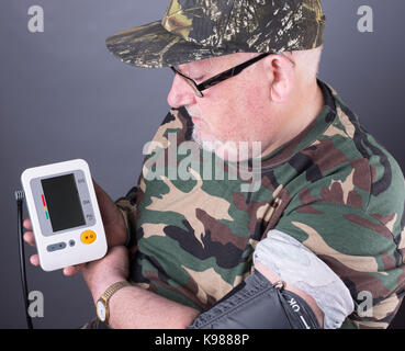 senior elderly man wearing camouflage clothing checking his blood pressure. blood pressure monitor testing in his - Stock Photo