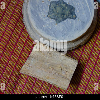 Thanaka wood and Kyauk pyin stone slab. Tanaka is Burmese tradition cosmetic made from bark of tanaka tree. - Stock Photo