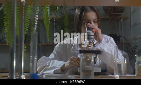 Young scientist looking through a microscope in a laboratory. Young scientist doing some research - Stock Photo