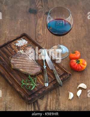 Cooked meat t-bone steak on serving board with garlic cloves, tomatoes, rosemary, spices and glass of red wine over - Stock Photo