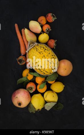 Mixed yellow orange fruit and veggies assortment, ingredients for smoothie. Melon, garnet, grapefruit, carrot, persimmon, - Stock Photo