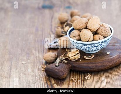 Walnuts in ceramic bowl and on cutting board with nutcracker over  rustic wooden background - Stock Photo