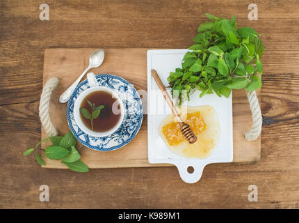 Cup of herbal tea with fresh mint and honey on wooden tray over rustic background. Top view. - Stock Photo