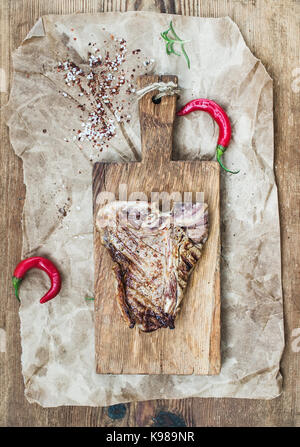 Cooked meat t-bone steak on serving board with red chili peppers, spices, fresh rosemary over oily craft paper and - Stock Photo