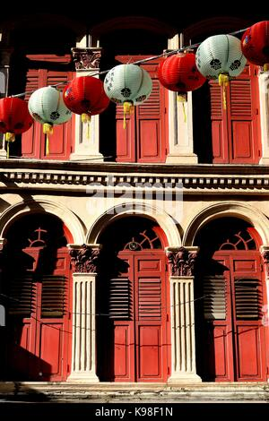 Traditional shop house exteriors with wooden louvered shutters and  ornate columns and carvings in the Joo Chiat - Stock Photo