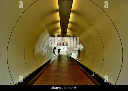 Perspective view along a curved pedestrian tunnel under the main road at Empress Place, Singapore - Stock Photo