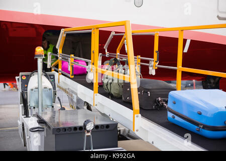 Suitcases On Moving Conveyor Attached To Airplane - Stock Photo