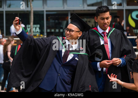 Higher Education in the UK: A group of foreign overseas Asian Aberystwyth University students wearing traditional - Stock Photo