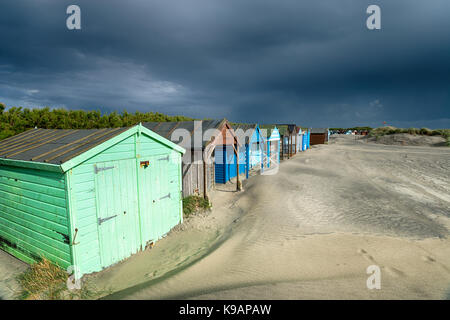 Dark storm clouds gather over colourful beach huts at West Wittering on the West Sussex coast - Stock Photo