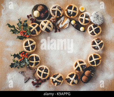 Mince Pies presented in a circle shape on a wooden chopping board. - Stock Photo