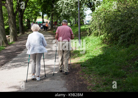 Powerful happy elderly people are walking with hiking sticks, canes - Stock Photo