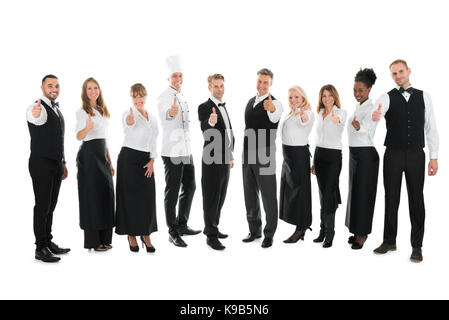 Full length portrait of confident restaurant staff standing in row against white background - Stock Photo