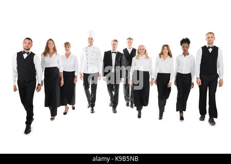 Full length portrait of confident restaurant staff walking in row against white background - Stock Photo