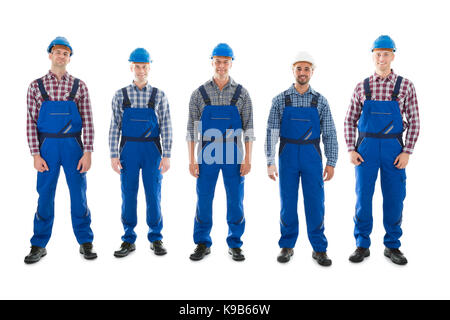 Full length portrait of confident male carpenters standing in row against white background - Stock Photo