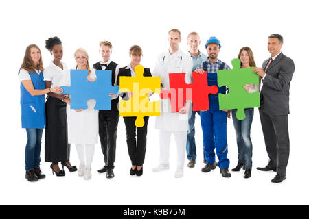 Portrait of confident people with various occupations holding jigsaw pieces while standing against white background - Stock Photo
