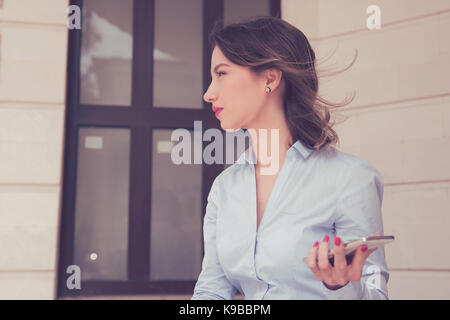 Frustrated annoyed sad woman with mobile phone standing outside apartment condo - Stock Photo