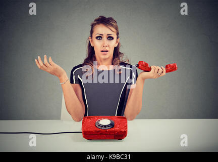 Shocked woman receiving bad news on the phone - Stock Photo