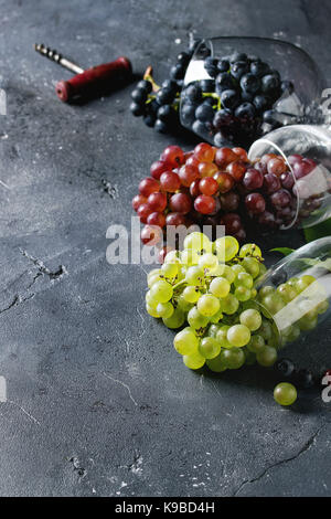 Variety of three type fresh ripe grapes dark blue, red and green in different lying wine glasses with old corkscrew - Stock Photo