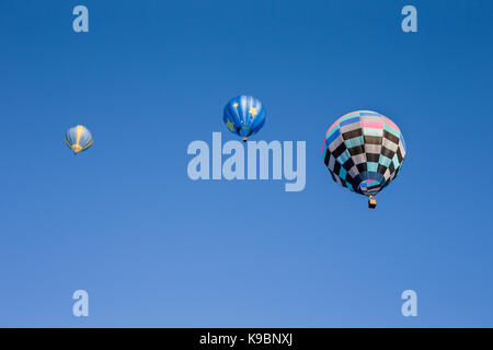 Three colorful hot air balloons set against a clear blue sky.  Seen from below.  Room for copy in the sky. - Stock Photo