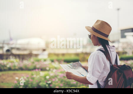 Happy women tourist on map to  the airport vacation.Travel concept. - Stock Photo