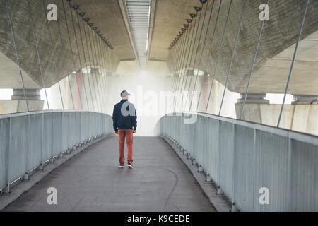 Man on the footbridge under highway bridge in mysterious morning fog. Prague, Czech Republic - Stock Photo