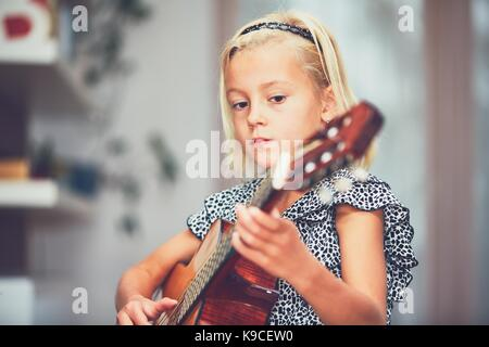 Little girl learning to play to the guitar at the home. - Stock Photo