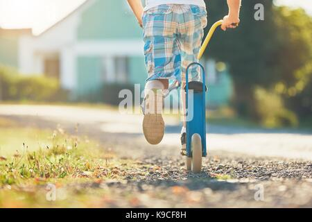 Summertime in the countryside. Little boy riding push scooter in sunny day. - Stock Photo