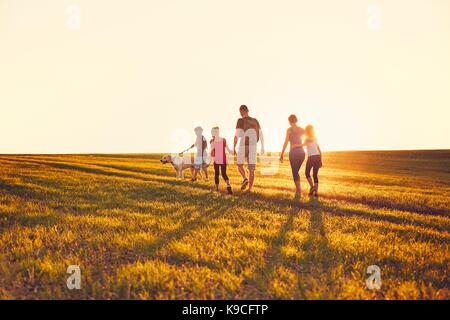 Summertime in the countryside. Silhouettes of the family with dog on the trip at the sunset. - Stock Photo