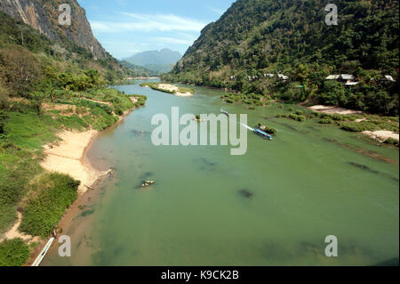 Two passenger boats make their way through a mountain ravine on the Nam Ou river to Nong Khiaw in north east Laos - Stock Photo