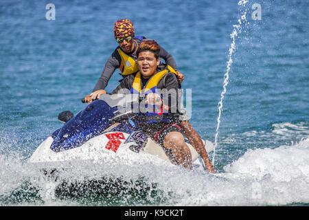 A teenage Filipino Asian boy has a lesson how to drive a water jet ski at White Beach, Puerto Galera, Oriental Mindoro - Stock Photo