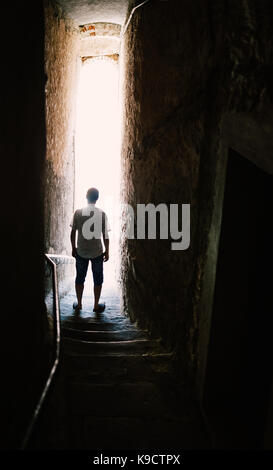 Man silhouette on stairs in narrow street. Mysterious concept - Stock Photo