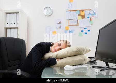office sleeping pillow. young businesswoman sleeping on pillow at desk in office stock photo p