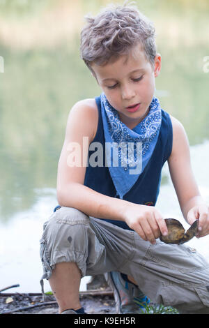 A Little Boy Of 3 Years Plays On The River Bank With