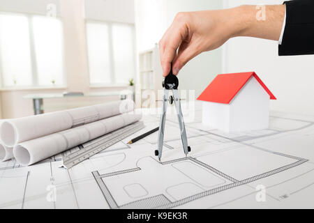Close-up Of Male Architect Hands Holding Compass On Blueprint - Stock Photo