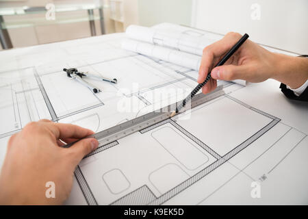 Close-up Of Engineer Drawing Diagrams With Pencil And Ruler On Blueprint Paper - Stock Photo