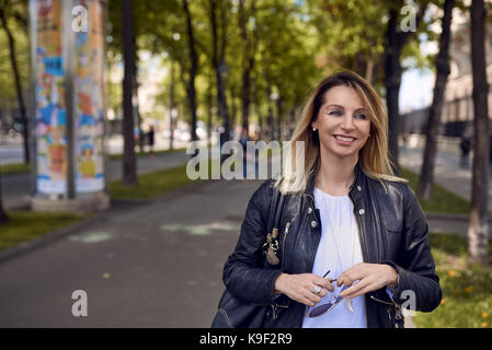 Outdoor portrait of smiling long-haired woman walking along sidewalk - Stock Photo