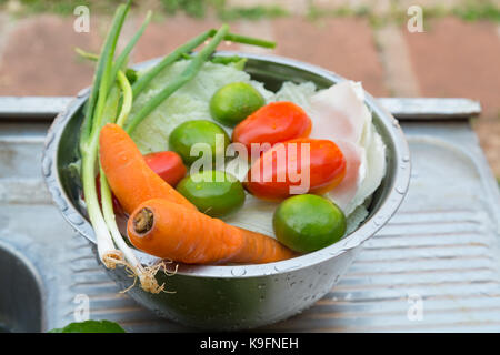 Vegetables (welsh onions, carrots, tomatoes, chinese cabbage) and fruit (lemons), mixed, fresh washed in metal bowl - Stock Photo