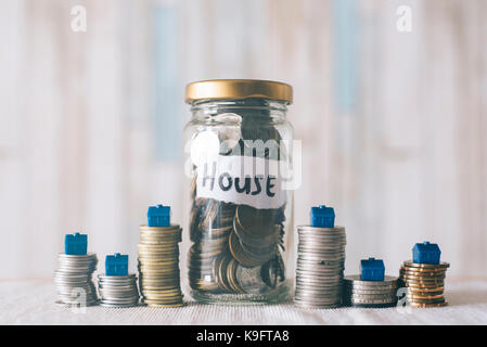 coins and glass jar on a table with miniature house, with a note written ' HOUSE '. Saving money to buy house. Saving - Stock Photo