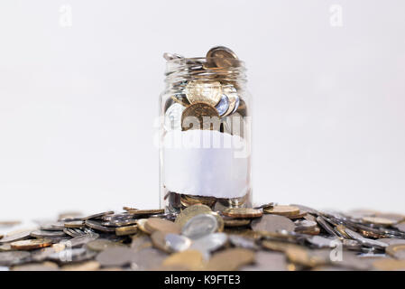 Glass jar filled with coins on a group of coins.attached with empty white paper. isolated on white background. financial - Stock Photo